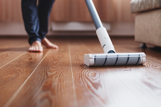ターボブラシコードレス掃除機のクローズアップは、家の寄木細工の床を掃除します。洗浄のための最新技術。