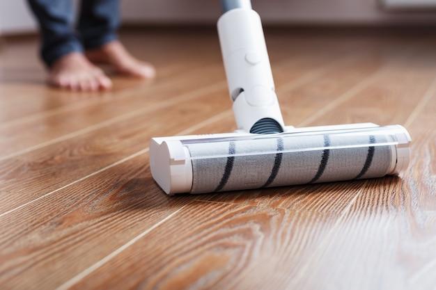 ターボブラシコードレス掃除機のクローズアップは家の寄木細工の床をきれいにします