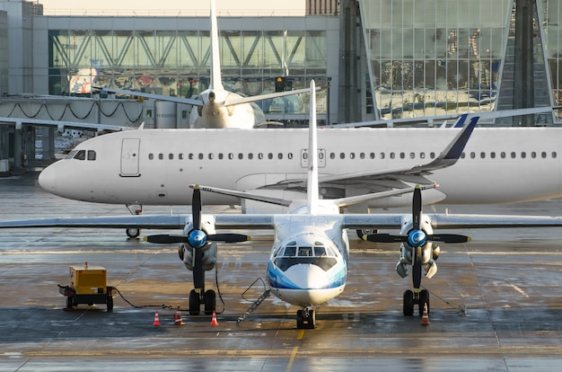 Turboprop aircraft parked behind the jet plane taxiing.