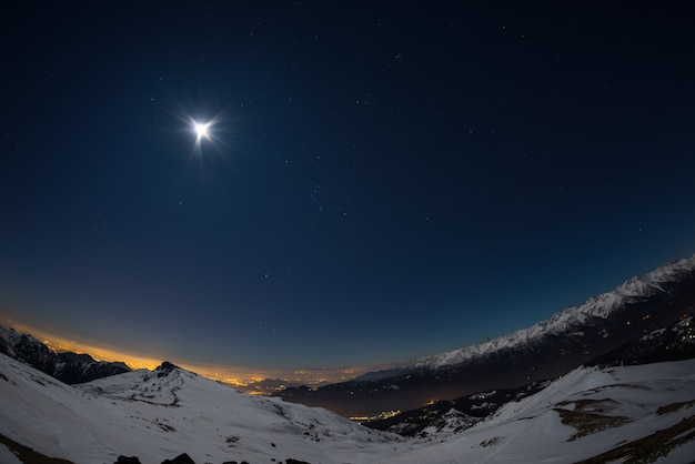 Turin city lights, night view from snow covered alps by moonlight. moon and orion constellation, fisheye