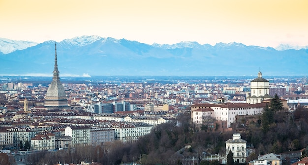 Turin, italy - circa august 2020: panoramic view with skyline at sunset. wonderful alps mountains in background.