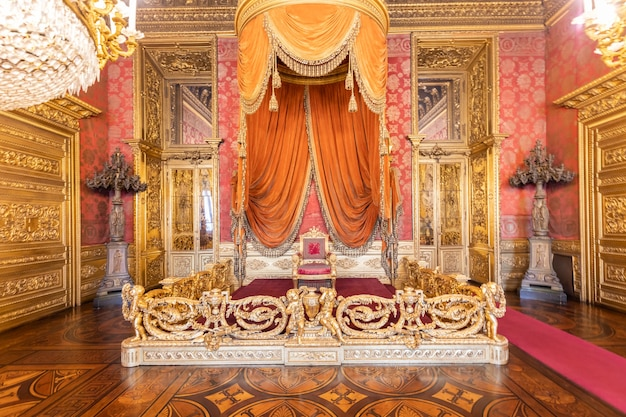 イタリア、トリノ-2021年8月頃:豪華な宮殿の椅子のある古い玉座の間のインテリア。赤と金のアンティークバロック様式-サボイア王宮