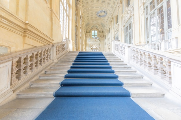 Turin, italy - circa june 2021: the most beautiful baroque staircase of europe located in madama palace (palazzo madama). interior with luxury marbles, windows and corridors.