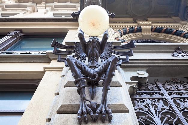 Турин, италия. таинственная лампа с гигантской горгульей на общественной улице, датированная примерно 1850 годом.