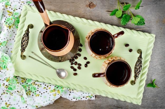 Турок и кофейные чашки на деревянном подносе. деревенский стиль
