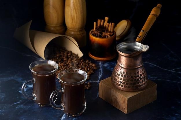 Турка и две чашки горячего кофе со специями и кофейными зернами на темном фоне