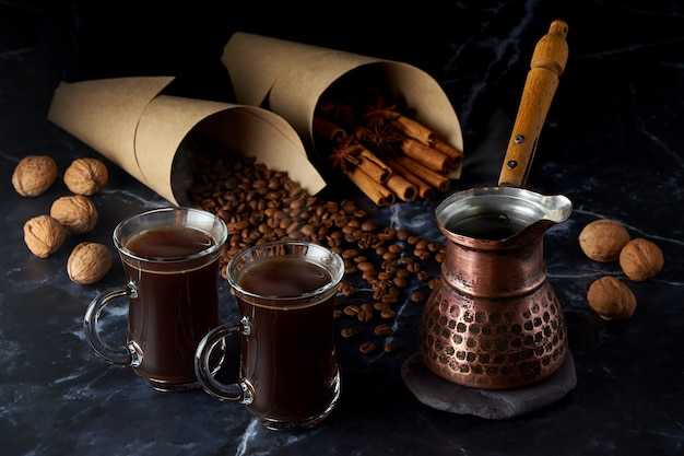 Turk and two cups of hot coffee with spices, nuts and coffee beans on a dark background