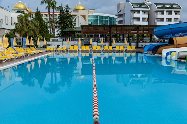 Turkey alanya may 05, 2019: a big outdoor pool with a lot of yellow lounges and umbrellas on both sides in the water park on a sunny day.