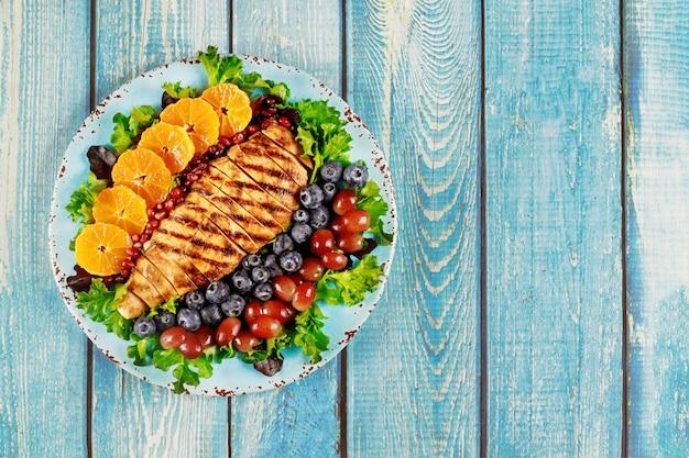 Грудка индейки с овощным салатом и мандарином, виноградом и черникой.