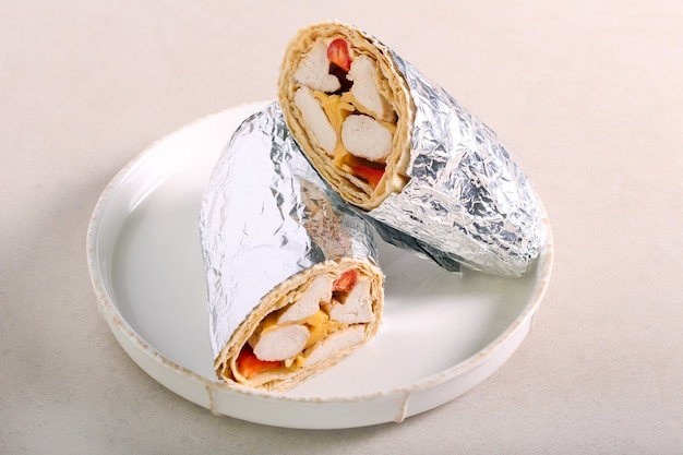 Turkey, cheese, tomato and pepper roll in foil, on plate