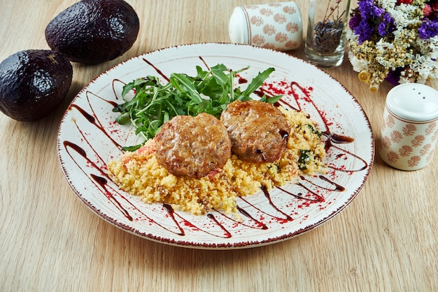 Turkey cutlets (burgers) with couscous garnish and pomegranate sauce on a white plate. diet fitness nutrition. healthy food. close up view