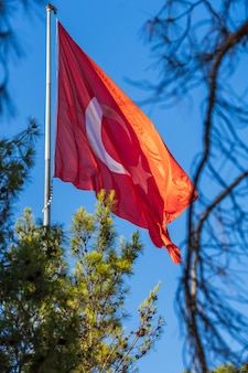 Turkey flag waving in the wind against a blue sky background.