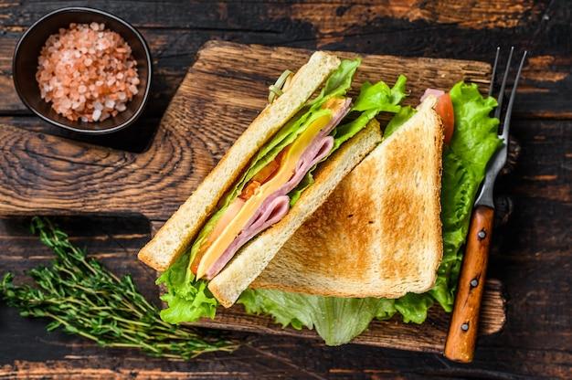 ターキーハムクラブは、木製のまな板の上にチーズ、トマト、レタスをサンドイッチします。暗い木の背景。上面図。