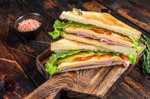 木製のまな板にチーズ、トマト、レタスをのせたターキー ハム クラブのサンドイッチ。