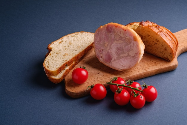 Turkey ham meat, fresh cherry tomatoes branch and loaf sliced bread on wooden cutting board, blue minimal wall, angle view, copy space