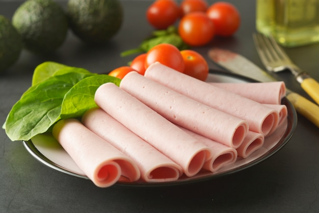 Turkey ham rolled on plate with fresh vegetables
