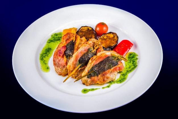 구운 야채와 페스토 소스와 함께 꼬치에 허브로 채워진 터키 메달리온. 파란색 배경에 흰색 접시에 평면 위치 최고보기.