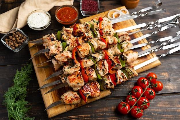 素朴な木製のテーブルにコショウ トマトとタマネギを金属の串に刺した七面鳥またはチキンのシシカバブ