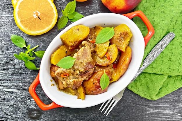 Индейка, тушенная с персиками, свежим острым перцем и апельсиновым соусом, листья базилика на сковороде, салфетка, фрукты на фоне деревянной доски сверху