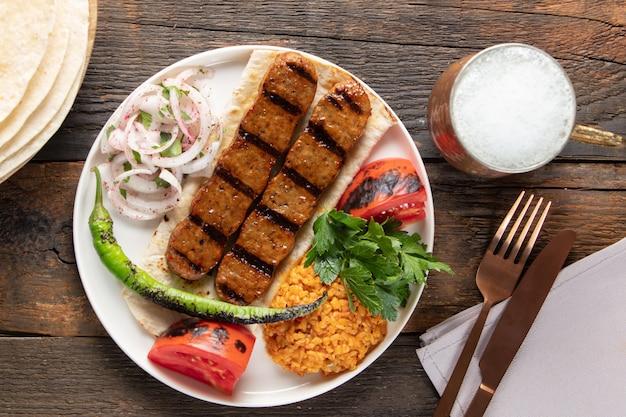 トルコ料理のアダナケバップとライスピラフと野菜の盛り合わせ