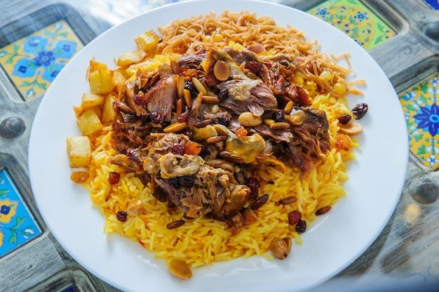 Турецкая и арабская традиционная печень донер кебаб с салатом, йогуртом, листьями салата, лавашом, луком, помидорами и рисом в белой тарелке на фоне гарнира ресторана