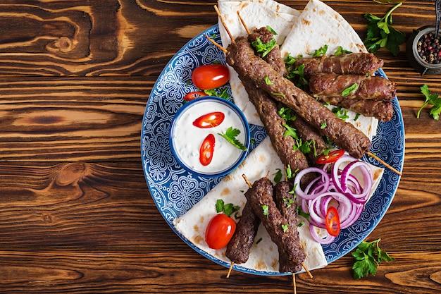 터키어와 아랍어 전통 라마단 믹스 케밥 플레이트. 케밥 아다 나, 닭고기, 양고기 및 쇠고기와 소스와 함께 lavash 빵에. 평면도