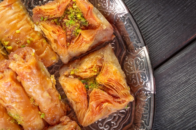 Turkish arabic dessert baklava with honey and nuts on a silver plate