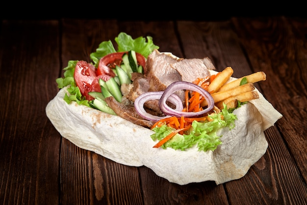 Turkish and arabic traditional mix kebab plate. kebab beef on lavash bread with sauce and vegetables.