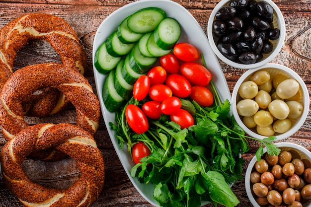 Turkish bagel in a pot with salad, pickles in bowls top view on a wooden surface