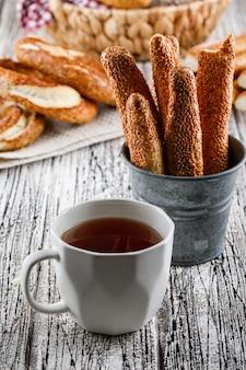 木の表面にお茶とパンの側面図のカップとトルコのベーグル