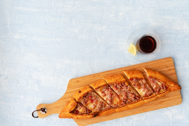 Turkish baked pide bread on light blue wooden surface
