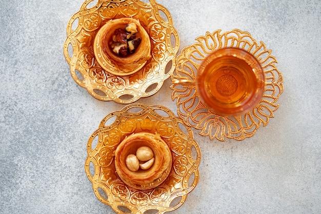 灰色の背景に東洋料理のトルコのバクラヴァとトルコのお茶