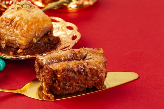 Turkish baklava and coffee in oriental dishware on red background