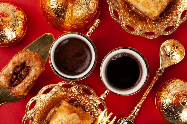 Turkish baklava and coffee in oriental dishware on red table