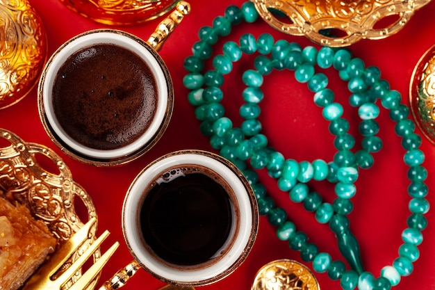 Turkish baklava and coffee in oriental dishware on red, top view