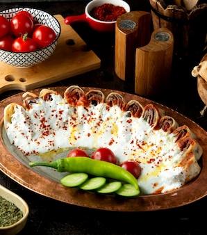 Кусочки турецкого говяжьего шашлыка, завернутые в лепешку, украшенные йогуртом и томатным соусом
