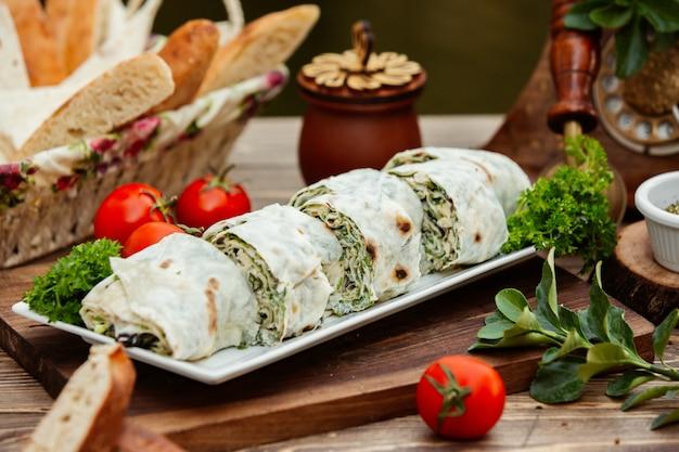 Слои турецкого бурака лепешки, завернутые со свежей зеленью и сыром