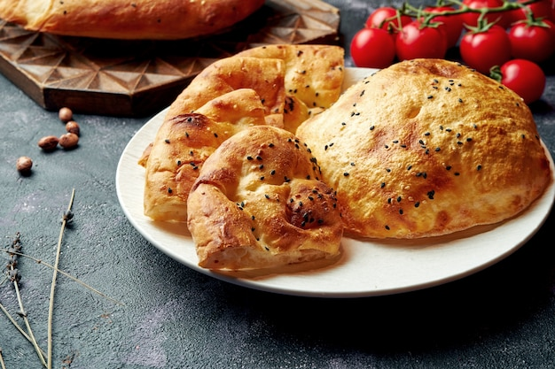 Турецкий хлеб (рамазан пидеси) - пышный экмек и лаваш на белой тарелке. рамадан лепешки