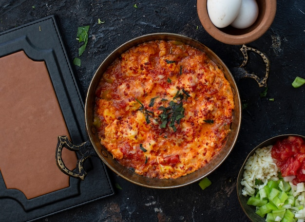 Turkish breakfast menemen in a pan, white boiled eggs and vegetable, tomato cucumber