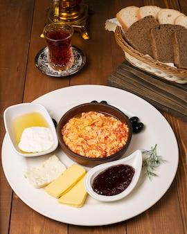 Turkish breakfast menemen with honey, cream, olives, jam and cheese variations in white plate and glass of tea