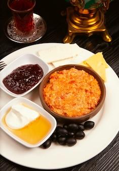 Turkish breakfast menemen with honey, cream, olives, jam and cheese variations in white plate.