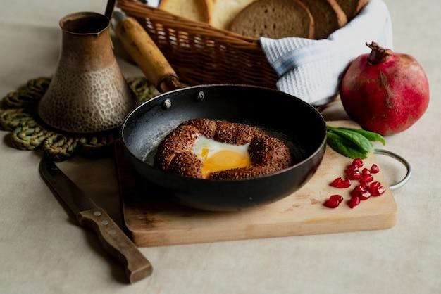 Турецкий завтрак, яичница в булочке simit на сковороде, кофе в турке, свежий хлеб