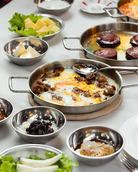 Turkish breakfast setup with egg and meat dish cooked in steel pan