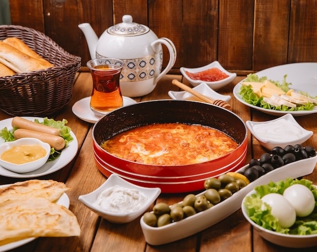 Turkish breakfast setup with egg and tomato dish sausages olives eggs cheese butter and tea