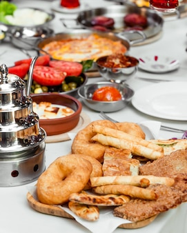Turkish breakfast setup with pastry platter with finger bourak and donuts