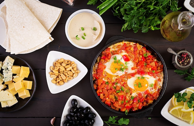 Turkish breakfast. shakshuka, olives, cheese and fruit. rich brunch.