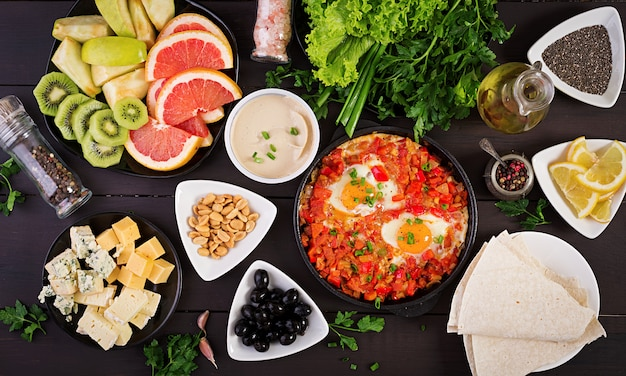 Turkish breakfast -  shakshuka, olives, cheese and fruit.