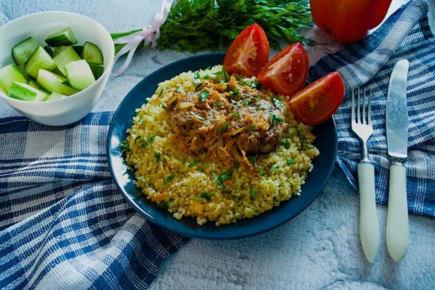 Turkish bulgur pilaf with meatballs and greens.