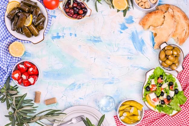 トルコのキャベツロールと各国料理のさまざまなスナック。ぶどうの葉とオリーブのご飯。伝統的なオリエンタルランチの食事。テキスト用の空きスペース、空のプレート