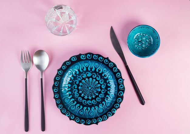 Turkish ceramics decorated blue plate with new luxury black cutlery on pink, top view